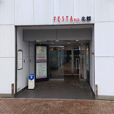 ファミリマートの横のフェスタ北館がございますので、エレベーターにて3階までお上がりください。